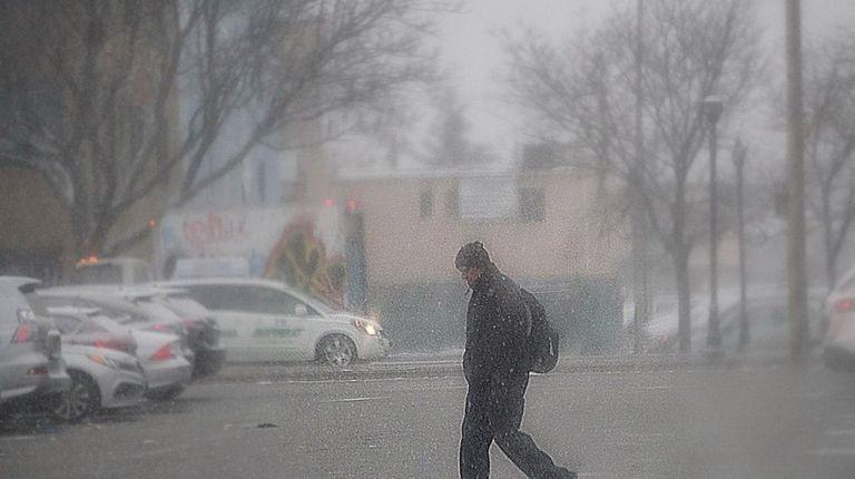 A pedestrian walks through a snow storm Saturday