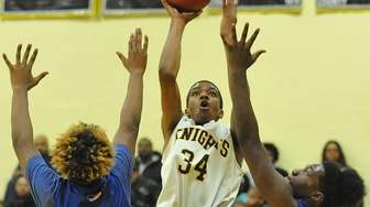 De'Shaun Jackson #34 of Uniondale, center, shoots a