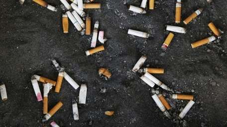An ashtray with cigarette butts is shown outside