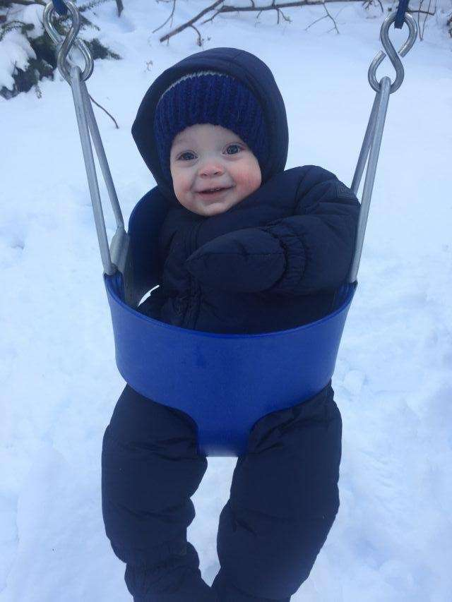 Brendan Rostron (10 months) swinging in the snow