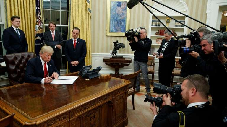 President Donald Trump signs his first executive order