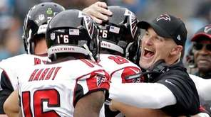 Atlanta Falcons head coach Dan Quinn, right, hugs