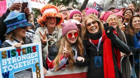 Gloria Steinem, with long red scarf, greets demonstrators