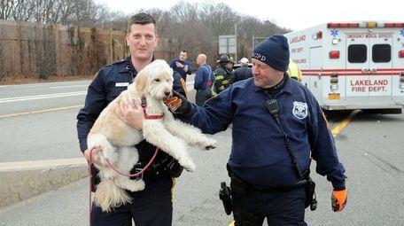 Suffolk County Officer Joseph Goss, left, carries Grace,