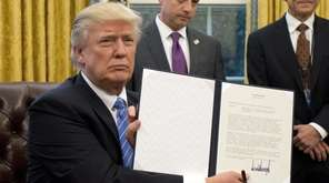 President Donald Trump shows the signed executive order