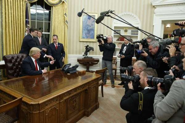 President Donald Trump hands over his pen after