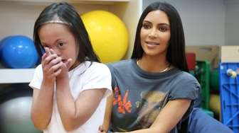 Kim Kardashian West sits with a disabled girl