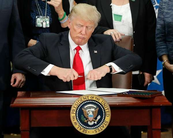 President Donald Trump prepares to sign an executive