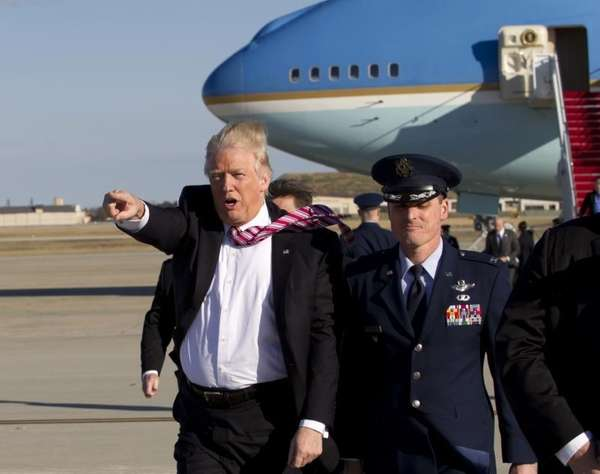 President Donald Trump walks on the tarmac as