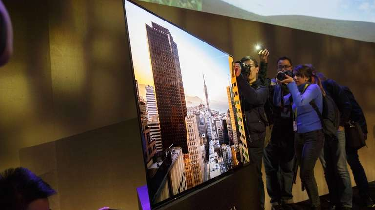 Attendees photograph a Sony Corp. XBR-A1E Bravia OLED