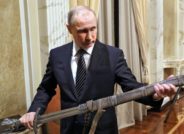 Russian President Vladimir Putin holds a film replica