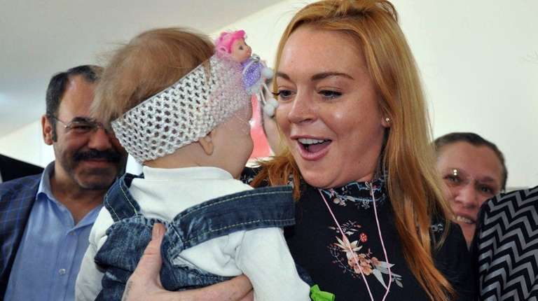 Lindsay Lohan holds a Syrian refugee child as