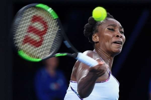 Venus Williams hits a return against Serena Williams