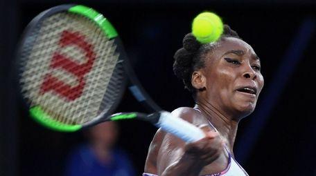 Venus Williams hits a return against Serena Williams