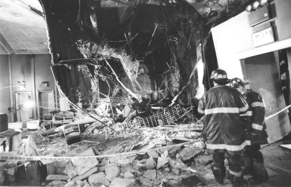 Firefighters examine damage to the lobby of the