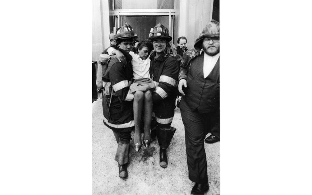 Firefighters carry an injured woman from the World
