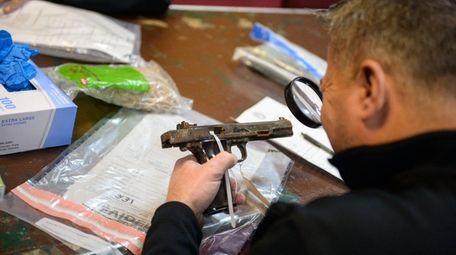 An investigator inspects a gun during the