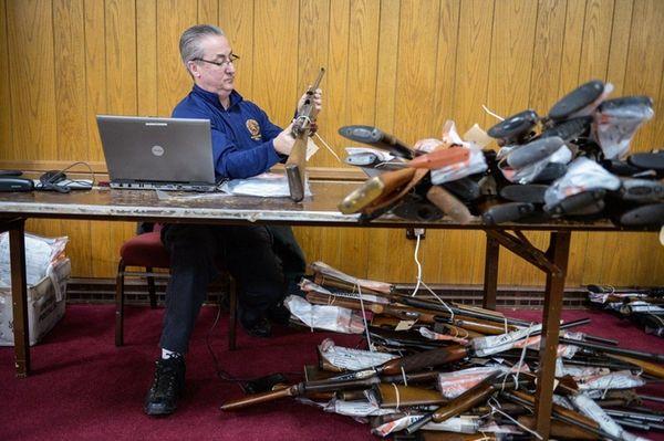 Nassau County investigator Robert McHugh enters a rifle