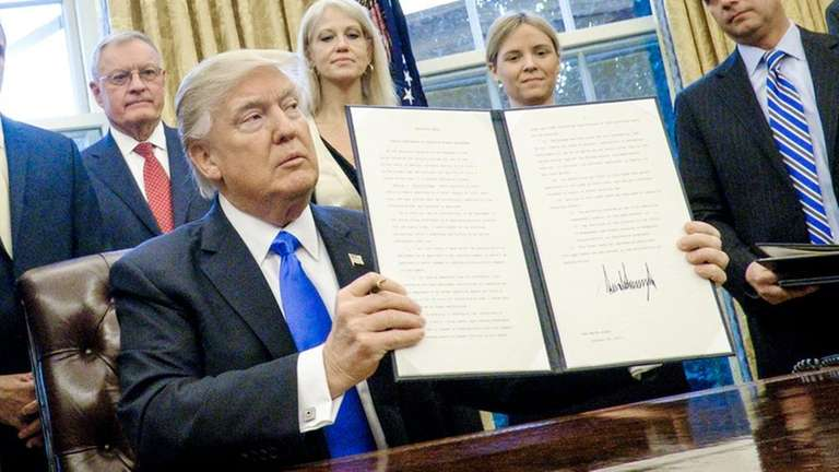 President Donald Trump holds up one of the