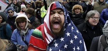 Izzy Berdan, center, wears an American flag as