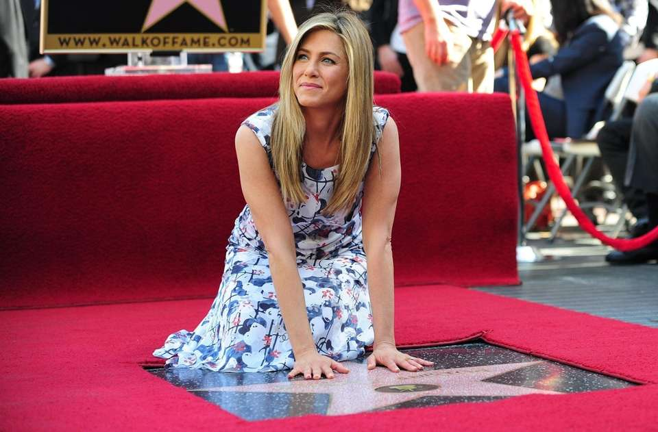 Jennifer Aniston touches her just unveiled Star on