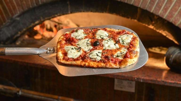 Margherita pizza emerges from the wood-fired brick oven