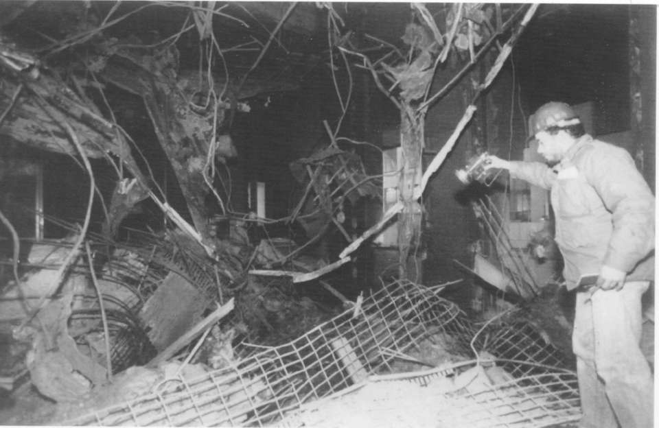 A workman checks the damage inside a room