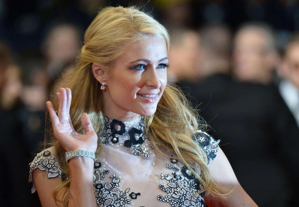 Paris Hilton waves as she arrives for the