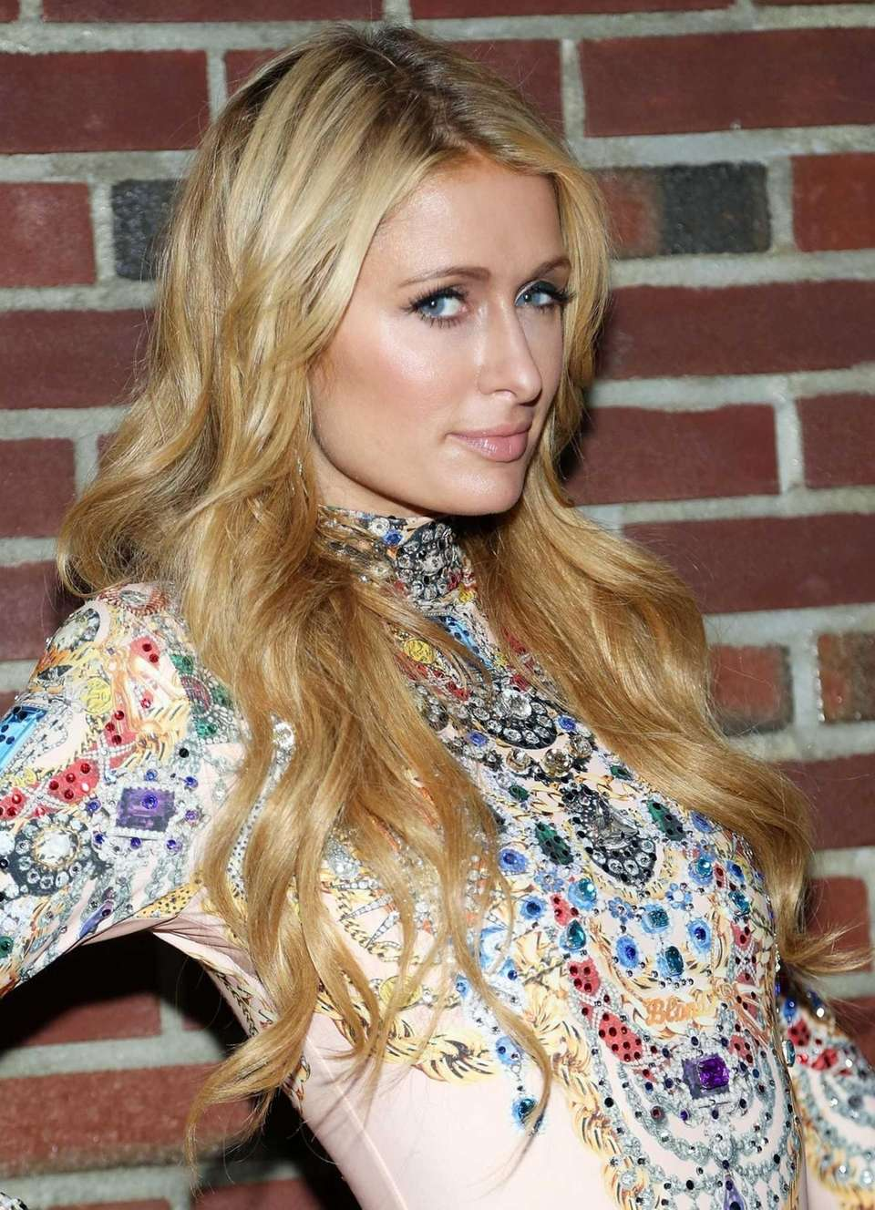 Paris Hilton poses for a photo backstage at