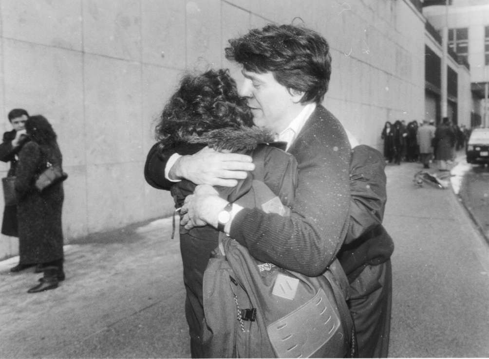 Office workers embrace on the street after evacuating