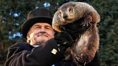 Groundhog Club handler John Griffiths, center, holds Punxsutawney
