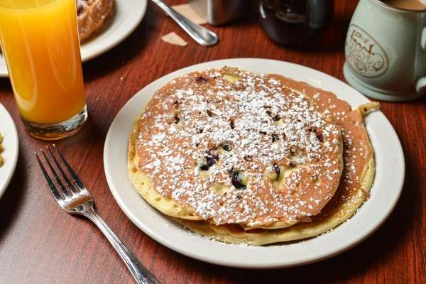 Blueberry pecan pancakes are dusted with powdered sugar