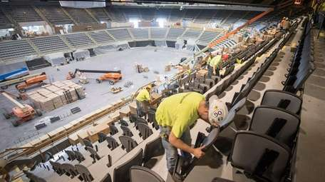 An Irwin Seating worker installs seats in the
