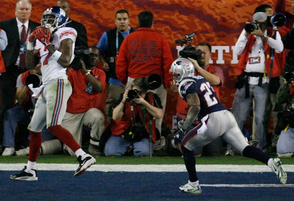 New York Giants receiver Plaxico Burress, left, scores