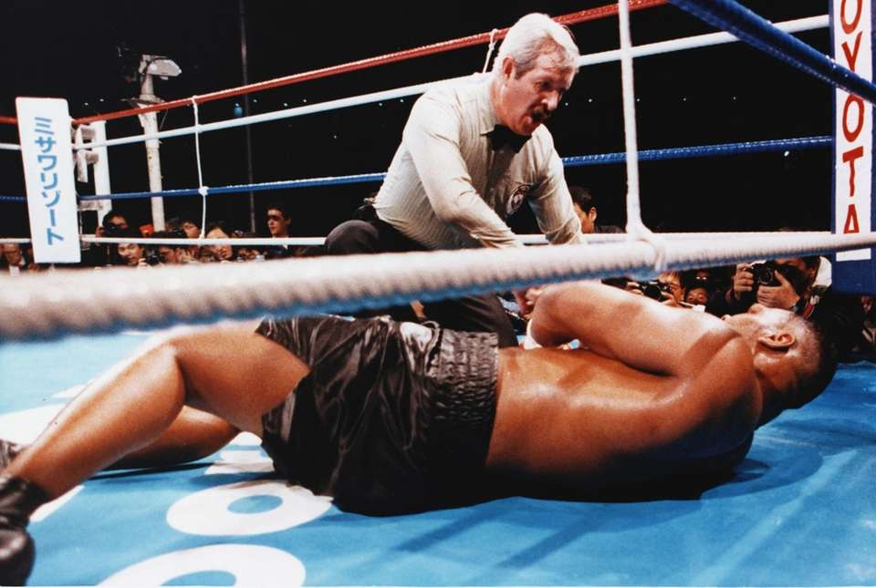 Referee Octavio Mayron counts as champion Mike Tyson