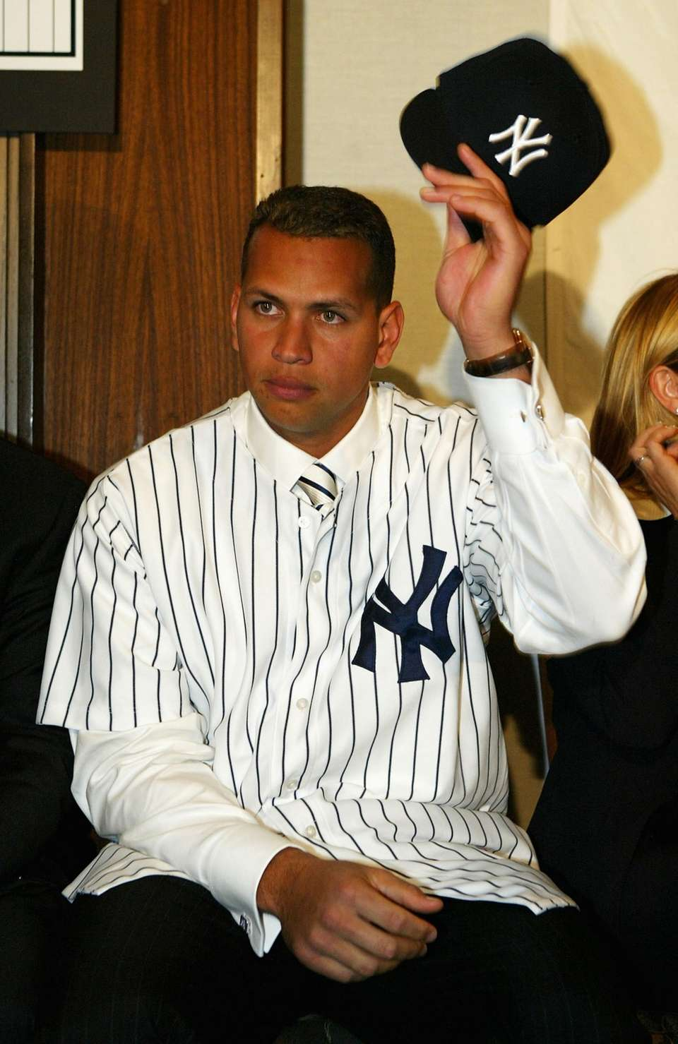 Alex Rodriguez tips his hat at a press