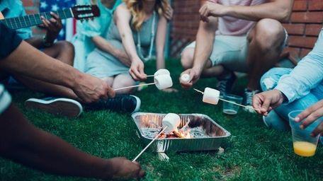 A family outside roasting marshmallows.