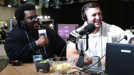 Craig Robinson, left, and Tim Tebow visit