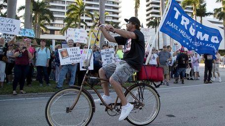 Dylan Moye rides his bike past Donald Trump