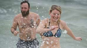 People run through the chilly ocean water during