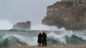 A couple watch the waves breaking in Nazare,