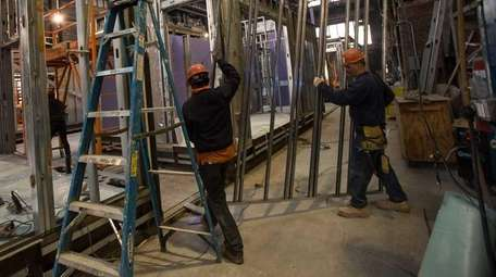 Carpenters install an already framed wall at the