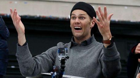 New England Patriots quarterback Tom Brady gestures beside
