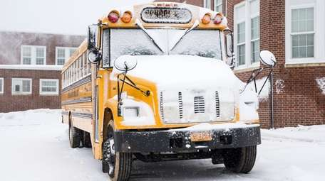 A snow-covered school bus parked beside Southold Junior-Senior