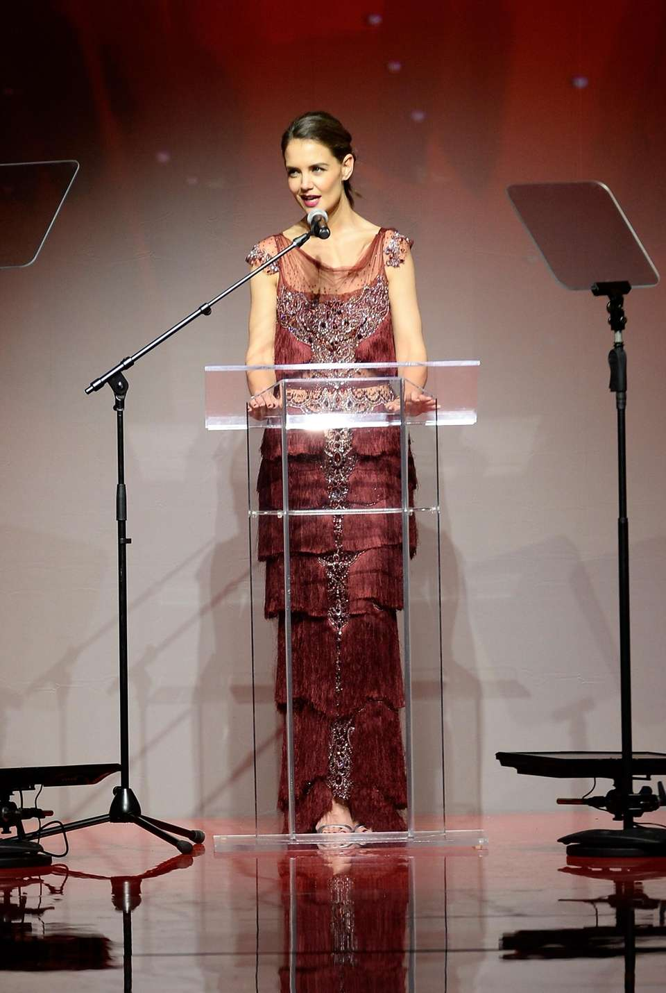 Katie Holmes speaks on the runway at the