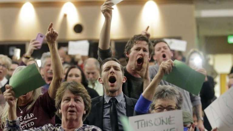 People shout to Rep. Jason Chaffetz during his