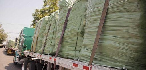 Bales of trash sit on flatbed trucks waiting