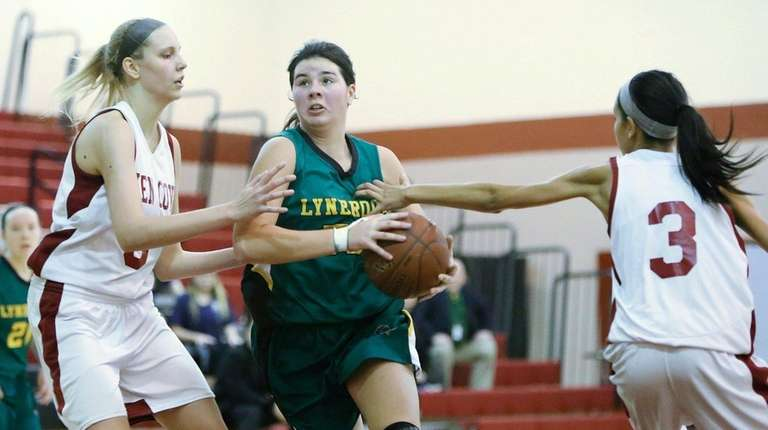 Lynbrook's Kerrin Montgomery, center, drives to the hoop