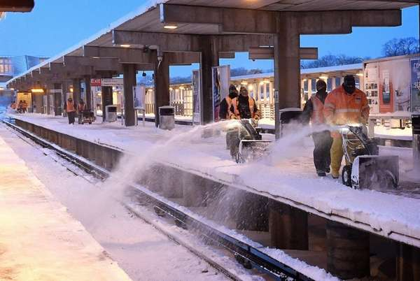 Long Island Rail Road personnel clear snow on