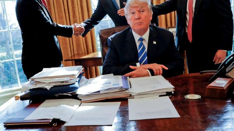 President Donald Trump sits at his desk after